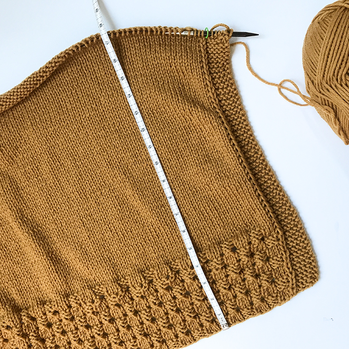 photo of the back of the Happy Harvest poncho with a tape measure to show the length